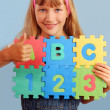 Schoolgirl with alphabet puzzle - Stock Photo