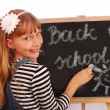 Schoolgirl writing on chalkboard — Stock Photo