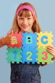 Schoolgirl with alphabet puzzle — Stock Photo