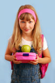 Schoolgirl with lunch box and apple — Stock Photo