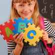 Schoolgirl holding letters puzzle — Stock Photo #6325932