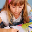 Schoolgirl learning to write letters — Stock Photo