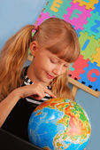 Schoolgirl with globe — Stock Photo