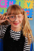 Schoolgirl with magnifying glass — Stock Photo