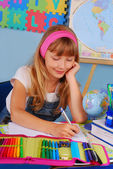 Schoolgirl writing in notebook — Stock Photo