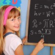 Genius schoolgirl writing on blackboard — Stockfoto