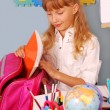 Schoolgirl packing her backpack — Stock Photo #6450846