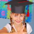 Schoolgirl in graduation cap — Stock Photo