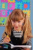 Smiling schoolgirl in the classroom — Stockfoto