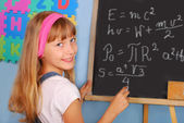 Genius schoolgirl writing on blackboard — Stock Photo