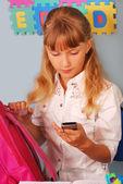 Schoolgirl using mobile phone — Stock Photo