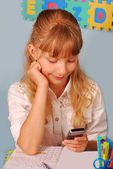 Schoolgirl using mobile phone during the lesson — Stock Photo