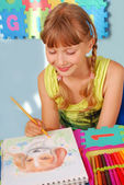 Young girl drawing a picture of dog — Stock Photo