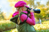 Young girl taking photos in autumn park — Stok fotoğraf