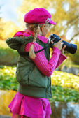 Young girl taking photos in autumn park — Stock Photo