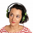 Stock Photo: Young woman listening music with headphones isolated on white background