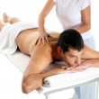 Man receiving massage relax treatment from female hands — Stock Photo