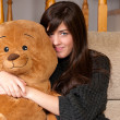 Young woman embracing teddy bear sitting on sofa close-up — Stock Photo