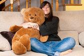 Young woman embracing teddy bear sitting on sofa — Stock Photo