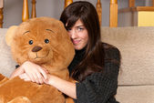 Young woman embracing teddy bear sitting on sofa close-up — ストック写真