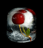 Cherry in ice on a black background — Stock Photo