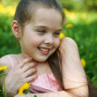 Stock Photo: Little girl sits on glade with dandelions