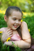Little girl sits on a glade with dandelions — Stock Photo