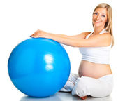 Pregnant woman excercises with gymnastic ball — Stock Photo