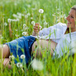 Pregnant woman sitting on green field — Stok fotoğraf