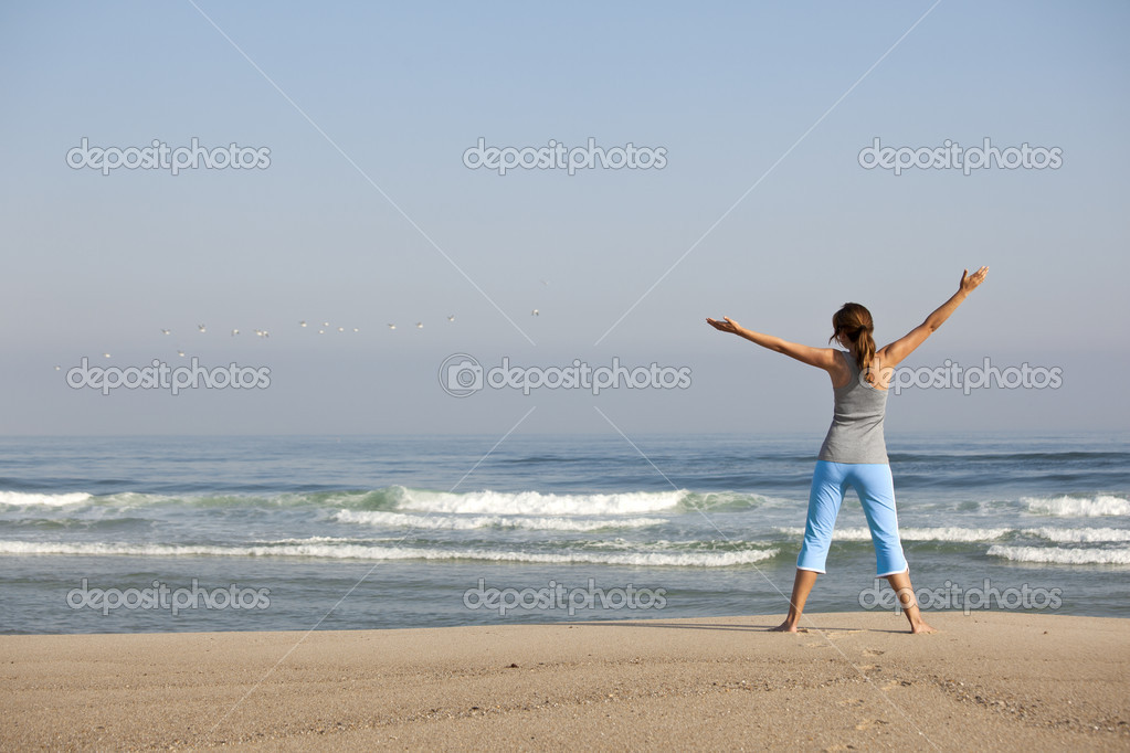Beautiful young woman with arms open, relaxing on the beach  Stock Photo #5547418