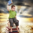 Stock Photo: Child sitting on books