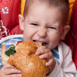 Little boy eating hamburger — Stock Photo