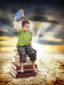 Child sitting on books — Stockfoto