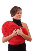 Woman embrace a heart-shape pillow — Stock Photo