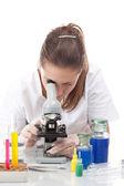 Vrouw die met een microscoop werkt — Stockfoto