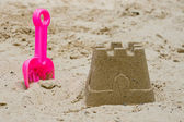 Sandcastle with a shovel — Stock Photo