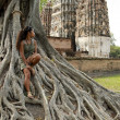 Woman sitting banyan tree sukhothai - Stock Photo