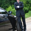 The young man with glasses and suit stand near to expensive car — Stock Photo