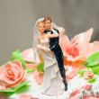 Embracing wedding couple. Figures on a cake — Stock Photo