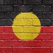 Flag of Aborigines on brick wall — Stock Photo