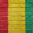 Flag of Guinea on brick wall — Stok fotoğraf