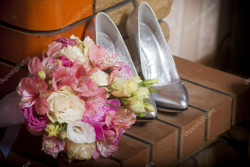Women's shoes and bouquet of flowers lay on the brick ledge — Stock Photo #6233893