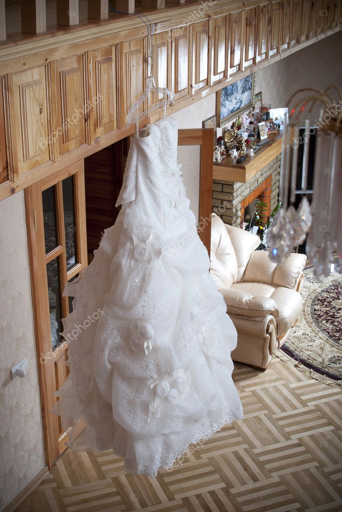 White wedding dress hanging on a hanger in the house — Stock Photo #6233900