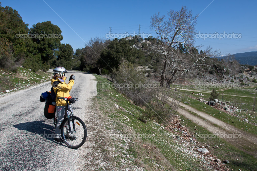 Cool girl riding a bicycle in the countryside and making photos. — Stock Photo #5945737