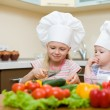 Two little girls preparing healthy food on kitchen — Stock Photo #6576981