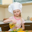 Little girl with oil preparing healthy food on kitchen — Stock Photo #6577001