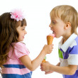 Girl shares, gives or feeds boy with her ice cream in studio iso — Stock Photo