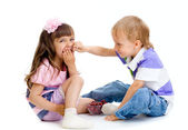 Boy feeds little girl with cherry berries in studio isolated — Stock Photo