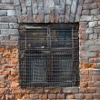 Window behind the iron shutters on the old brick wall — Stock Photo