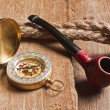 Compass and a pipe with a rope — Stock Photo #5766260